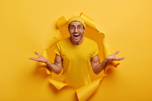 Horizontal shot of friendly looking happy caucasian man spreads hands sideways, presents something cool, dressed in casual clothes, poses in paper hole alone
