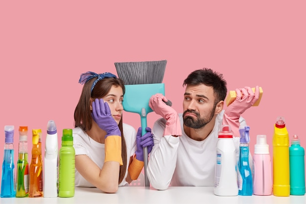 Horizontal shot of frustrated busy woman and man being overworked and stressed, carry brush, use necessary supplies for cleaning