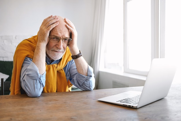 Horizontal shot of frustrated senior caucasian male employee with gray beard and eyewear holding hands on his bald head, having panic look, feeling stressed because of deadline. age and job