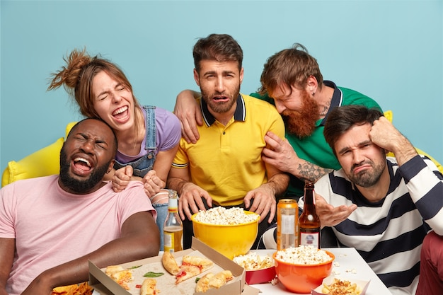 Horizontal shot of funny friends watch humor tv show, express different emotions, enjoy comedy film