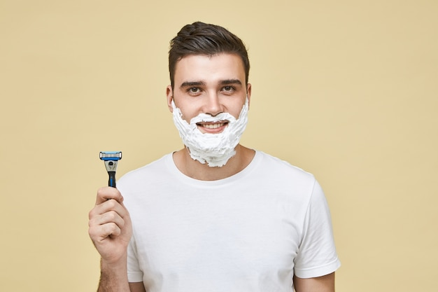 Horizontal shot of funny handsome young male with white foam on his face with smile, holding shaving stick, going ti shave beard, doing morning routine. grooming and men's beauty