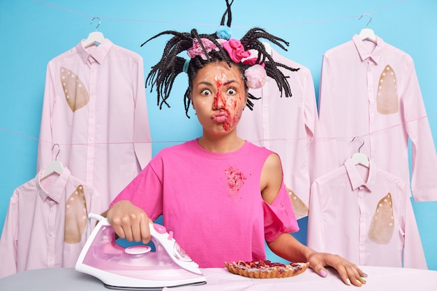 Horizontal shot of funny housewife busy doing daily domestic chores cooks pie irons laundry being dirty after housework poses against ironed burnt shirts hanging on rope over blue wall
