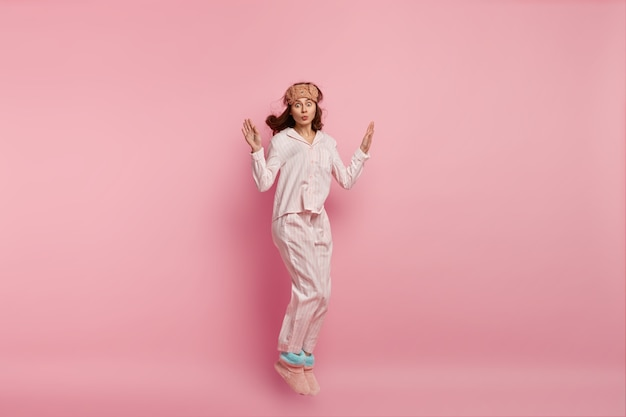 Horizontal shot of funny woman dressed in domestic clothing, has fun before sleep