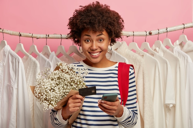 Horizontal shot of glad curly haired girl smiles pleasantly, uses modern gadget for paying online, holds bank credit card