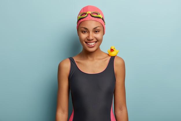 Inquadratura orizzontale del nuotatore femminile felice in posa con gli occhiali di protezione
