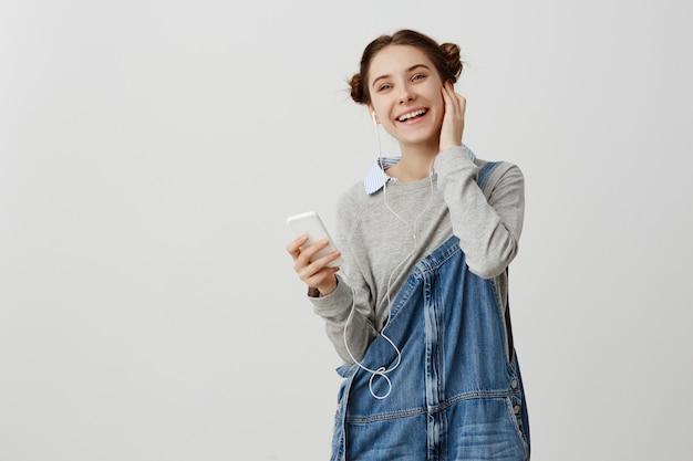 Colpo orizzontale della donna felice con i panini di odango che ascolta la musica ritmica tramite le cuffie. fashionista femminile che esprime felicità e piacere facendo uso dello smart phone che posa sopra la parete bianca. copia spazio