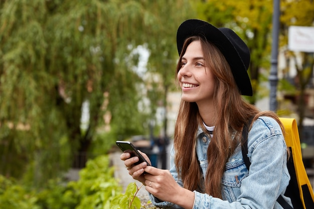 Horizontal shot of glad young teenage girl chats with friend via cell phone, installs app on gadget, wears fashionable black hat
