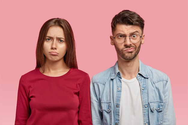 Inquadratura orizzontale di cupa donna e uomo con espressioni perplesse