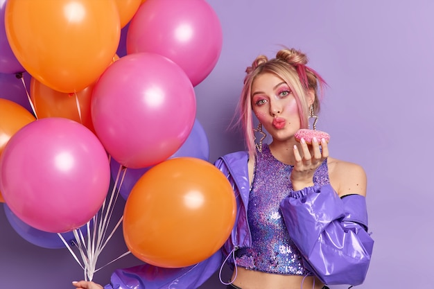 Horizontal shot of good looking blonde woman keeps lips folded holds glazed doughnut dressed in stylish clothes has bright makeup holds inflated colorful balloons