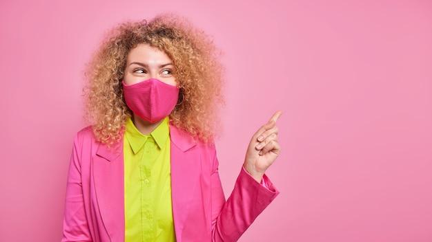 Il colpo orizzontale di bella donna dai capelli ricci allegra indossa la maschera facciale indica nell'angolo in alto a destra dimostra lo spazio per la tua pubblicità isolata sul muro rosa. misure preventive