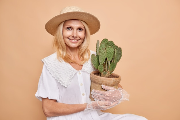 Horizontal shot of good looking lady with aristocractic manners wears stylish outfit carries potted cactus to her home garden smiles pleased sits indoor against brown wall