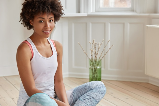 Horizontal shot of good looking relaxed woman with afro hairstyle, sits in lotus pose