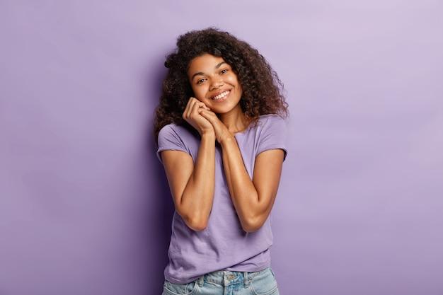 Horizontal shot of good looking tender dark skinned woman has curly hair, tilts head, has romatic date with boyfriend