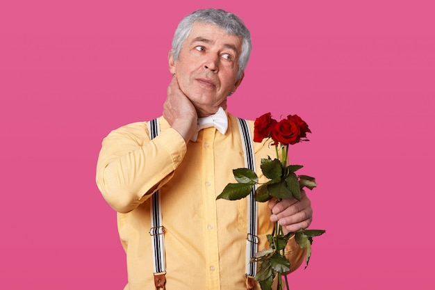 Horizontal shot of grey haired elderly man in formal fashionable clothes, keeps hand on neck, has pain, looks aside, holds red roses