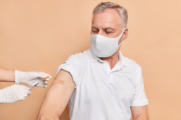 Horizontal shot of grey haired man gets vaccine to help immune system develop protection from coronavirus wears protective disposable mask casual white t shirt gets consultation from doctor