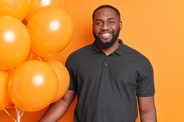 Horizontal shot of handsome afro american dressed casually expresses happy emotions poses with many air balloons isolated on orange wall celebrates his birthday spends free time on balloon party