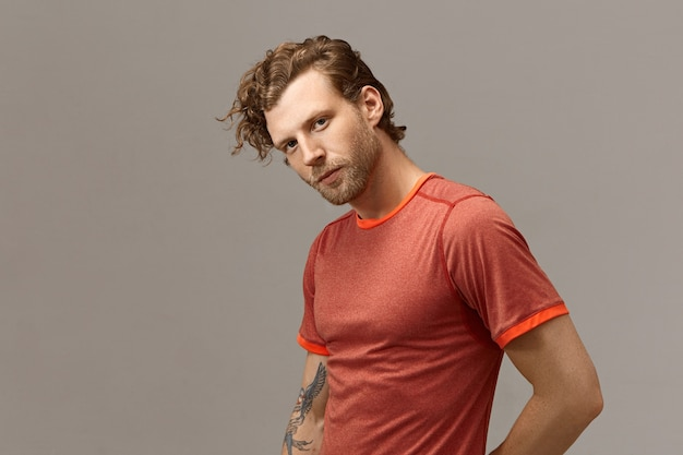 Horizontal shot of handsome bearded european guy with fit athletic body going to have running exercise, posing isolated at blank wall with copyspace for your promotional information