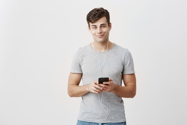 Horizontal shot of handsome caucasian guy dressed casually, holds modern smart phone, listens melodies in earphones, enjoys free internet connection, has happy expression, poses in studio