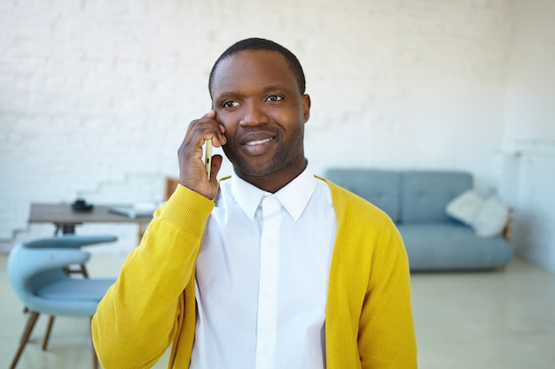 Horizontal shot of handsome cheerful african young man wearing white shirt and yellow cardigan, smiling broadly while having nice phone conversation, talking to friend, receiving good positive news