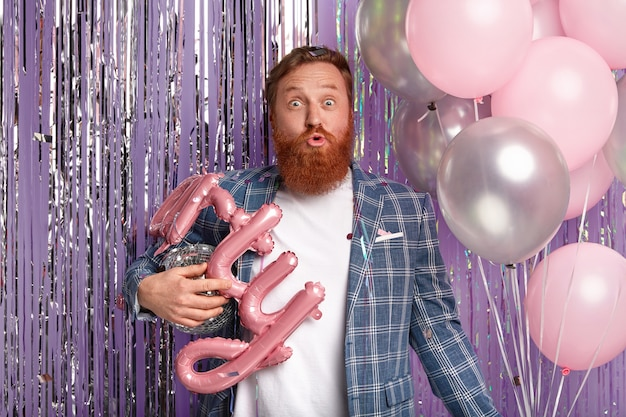 Horizontal shot of handsome ginger man with bristle, opens eyes widely, has folded lips, holds air balloons, prepares decoration for party, wears elegant clothes, stands indoor. celebration concept