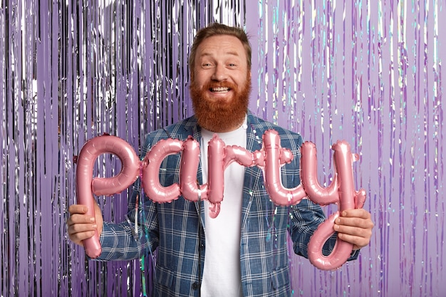 Horizontal shot of handsome man with thick red beard, poses with pink party balloons in form of letters, wears fashionable checkered jacket, has special event of festive occasion stands against tinsel