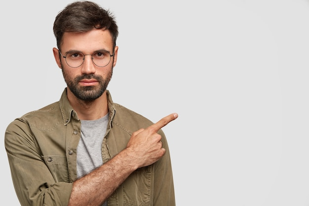 Horizontal shot of handsome unshaven young male with dark stubble, strict look, has serious expression, dressed in fashionable shirt, points right aside