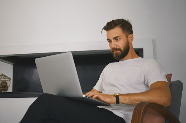 Horizontal shot of handsome young male freelancer with thick beard sitting in armchair with generic laptop computer, working remotely from home. people, gadgets, technology and communication concept