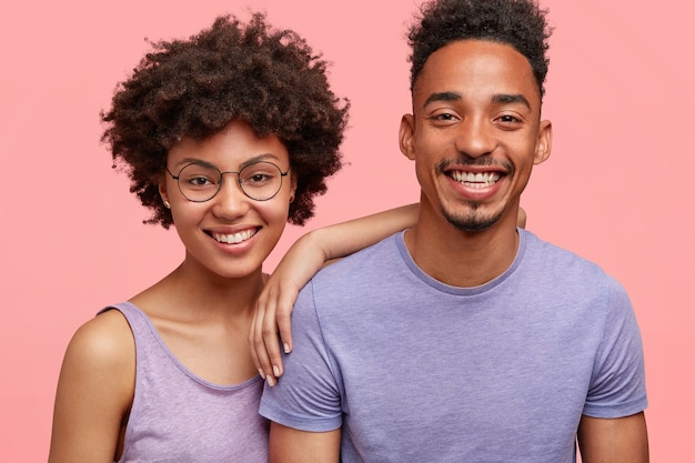 Horizontal shot of happy african american woman and man have truthful relationships, toothy smile, happy to meet with friends, dressed casually, isolated over pink wall. emotions concept