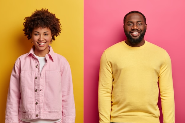 Horizontal shot of happy african american woman and man smile satisfied, stand next to each other against two colored wall, glad to hear excellent news from interlocutor, work as team.