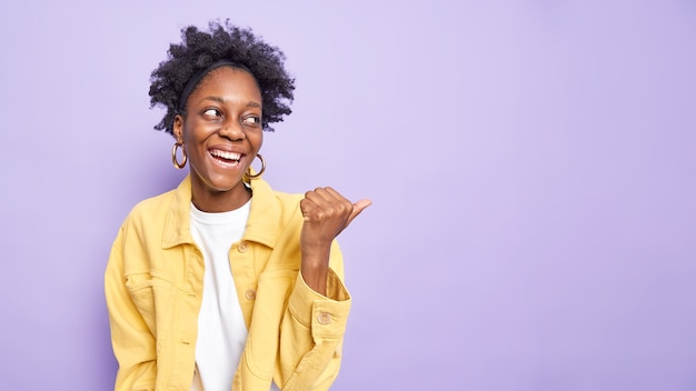 Horizontal shot of happy afro american woman points away with thumb shows advertisement on product at copy space