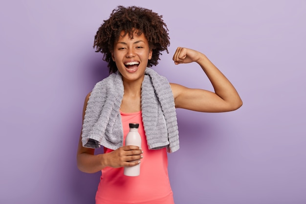 Horizontal shot of happy afro woman shows biceps, satisfied after active training