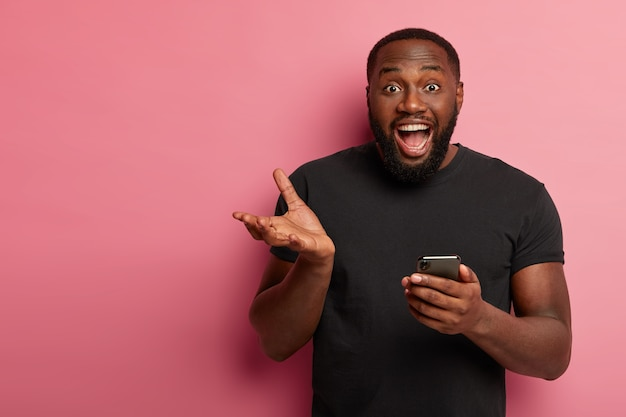 Horizontal shot of happy black man uses modern mobile phone, gestures with hand, exclaims from positive emotions, gets nice message, wears black t shirt