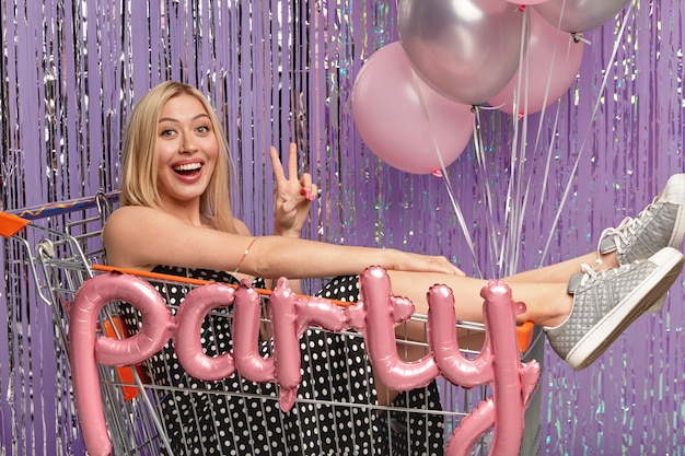 Horizontal shot of happy blonde female in shopping cart, makes peace gesture, wears dress and sportshoes, has fun on party with balloons, isolated over purple wall. festive day concept