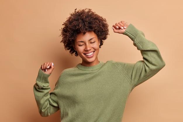 Il colpo orizzontale della donna dai capelli ricci felice si sente vivace e balla spensierata, tiene le braccia alzate, lancia la festa e gode della libertà vestita con un maglione casual isolato sopra il muro marrone