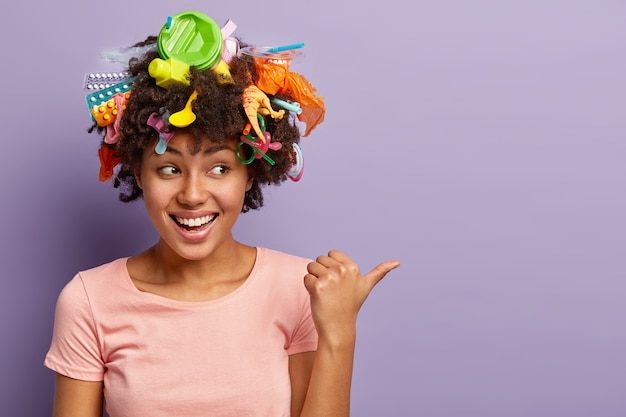 Horizontal shot of happy dark skinned woman with litter in hair, points thumb aside, demonstrates copy space, laughs positively, being active volunteer, wears casual t shirt. garbage and recycling