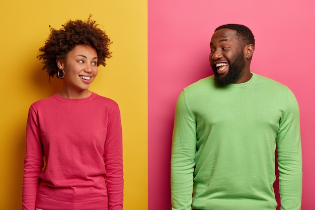 Horizontal  shot of happy ethnic woman and man look positively at each other, have happy faces, dressed in casual wear, isolated over yellow and pink backgroud. people, friendship concept