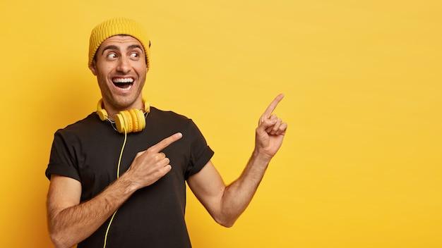 Il colpo orizzontale dell'uomo europeo felice indica da parte con due dita indice, vestito con un'elegante usura nera e gialla, indossa cuffie moderne intorno al collo per ascoltare la canzone