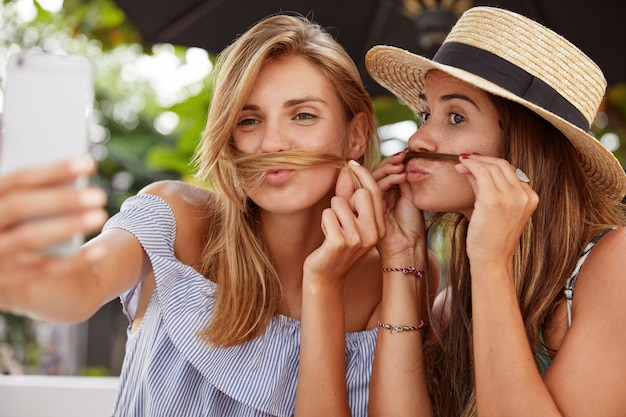Horizontal shot of happy females make selfie, have fun together, being in high spirit, foolish together outdoor, have rest during summer vacations. homosexual couple make photo for social networks