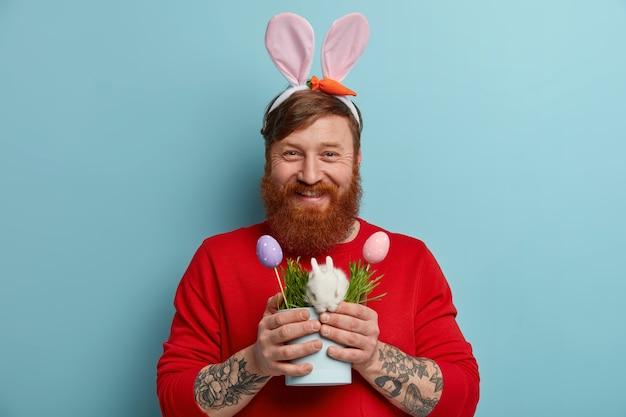 Colpo orizzontale del ragazzo hipster allo zenzero felice esprime emozioni positive, indossa orecchie da coniglio, ha un tatuaggio, tiene la pentola con un piccolo coniglio e due uova decorate, simboli della pasqua. concetto di vacanza.