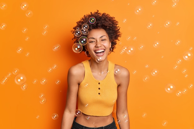 Colpo orizzontale di felice gioiosa giovane donna con i capelli ricci afro sorrisi ha ampiamente l'umore ottimista esprime emozioni e sentimenti sinceri