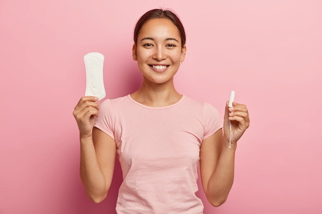 Horizontal shot of happy korean woman holds sanitary napkin and tampon, demonstrates intimate products for women health, smiles gently , dressed in casual outfit, has critical days.