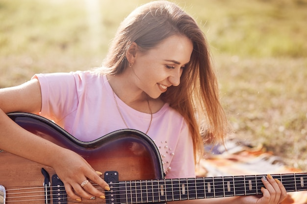 Horizontal shot of happy lovely female with positive smile plays guitar, learns new song, recreats oudoor in meadow, dressed in casual t shirt, has joyful expression. people, music, rest concept