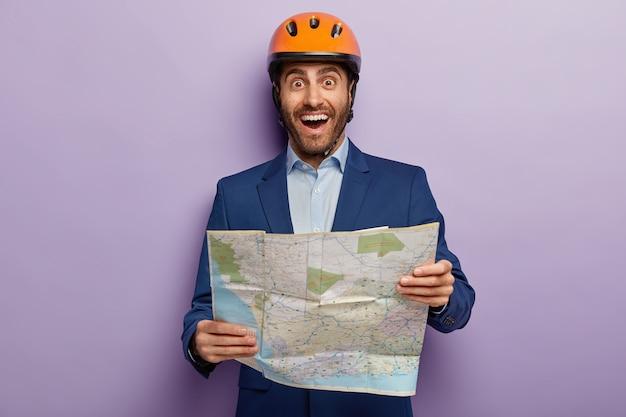 Inquadratura orizzontale di felice architetto maschio con mappa, studia la mappa della posizione in cui si trova il cantiere, indossa un elmetto protettivo, abbigliamento formale