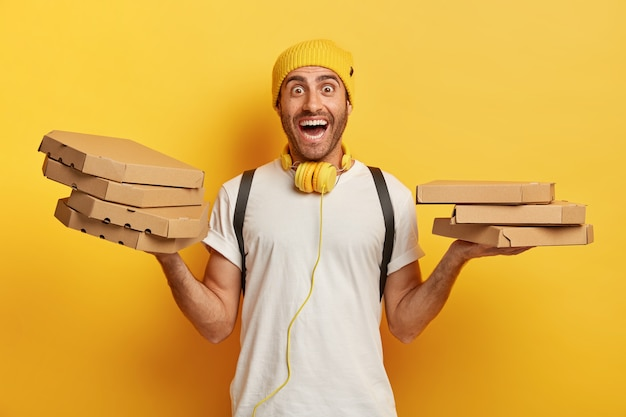 Horizontal shot of happy man holds two piles of carton boxes with pizza, has surprised joyful expression, works as courier in local restaurant