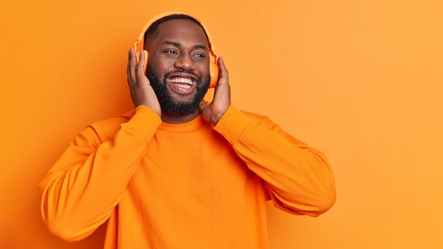 Horizontal shot of happy man keeps hands on stereo headphones smiles broadly enjoys pleasant song spends free time listening music isolated over vivid orange wall with blank space
