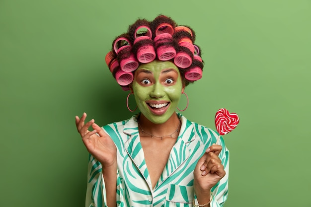 Horizontal shot of happy positive african american woman looks gladfully, giggles and undergoes beauty treatments, applies beauty mask, holds delicious lollipop, wears hair curlers, isolated on green