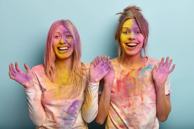 Horizontal shot of happy positive young women raise palms, stand next to each other over blue space