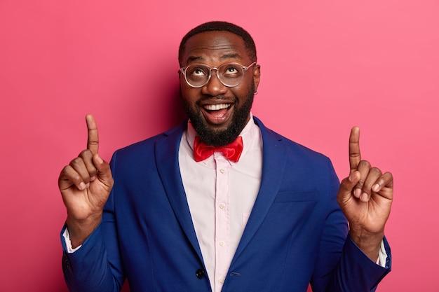 Il colpo orizzontale dell'impiegato afroamericano con la barba lunga felice indica lo spazio della copia sopra, mostra qualcosa sul muro bianco, vestito elegantemente