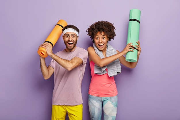 Horizontal shot of happy woman and man have fun after aerobics, raise hands with folded karemats, dressed in sportwear, enjoy spare time for sport, isolated on purple wall. diverse couple