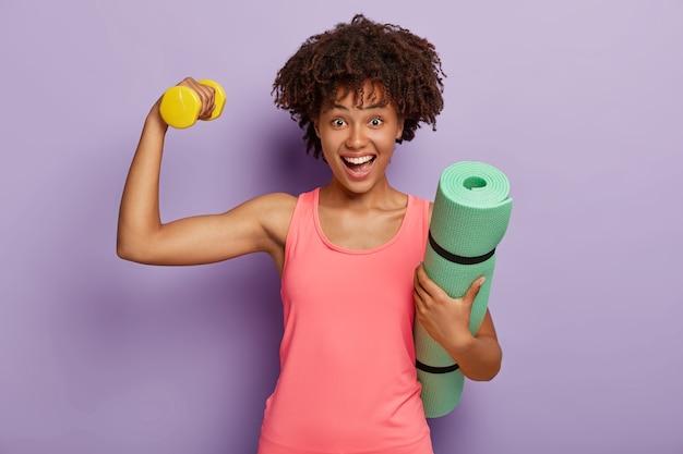 Colpo orizzontale di donna felice con acconciatura afro, solleva il peso per avere i bicipiti, porta il tappetino fitness arrotolato, indossa un giubbotto rosa, guarda felicemente, modella contro il muro viola. sport, motivazione